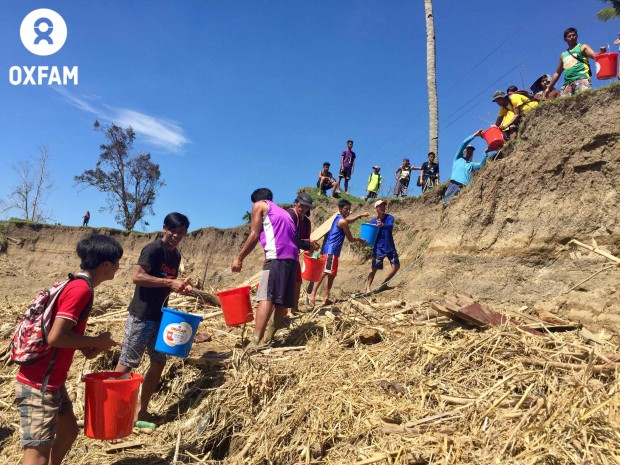 Locals form a human chain by the Chico river to bring the relief aid to higher ground in Barangay, Lipatan, Santo Nino town in Cagayan. Photo by April Bulanadi/Oxfam