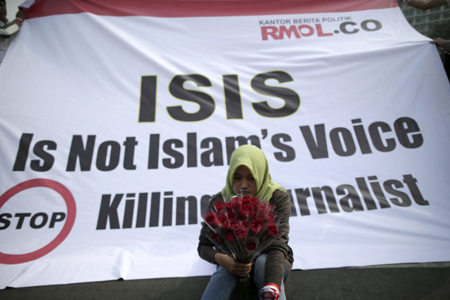 NOT ISLAM'S VOICE. An Indonesian journalist holds flowers as she sits in front of a banner during a protest against the killing of journalists by the Islamic State (ISIS) militant group, in Jakarta, Indonesia, September 5, 2014.