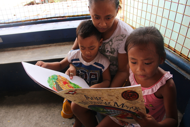 THE READER. Bianca reads with her mother and brother. Children are encouraged to start reading at an early age to prepare them for lifelong learning. Photo by Ella Carino/Save the Children