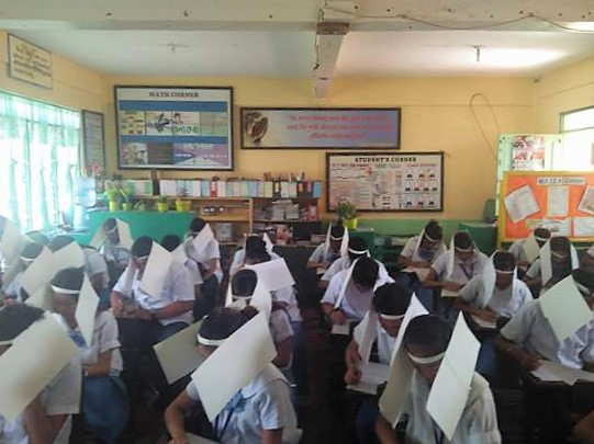 COVERED. Students are wearing folder-made head coverings while taking an exam. All photos by Jurinda Manaug