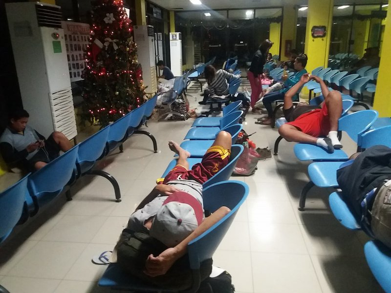 STRANDED. At a port in northern Mindanao, stranded passengers lie down on benches as they wait for the resumption of maritime trips. Photo courtesy of the Philippine Coast Guard