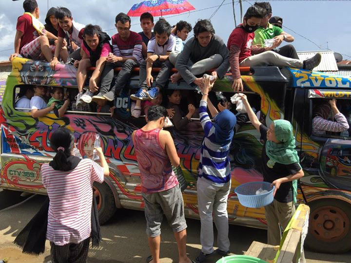 COMMUNITY. Balo-i residents band together to give out water and food to Marawi residents fleeing their homes for safety. All photos courtesy of Amer Riga