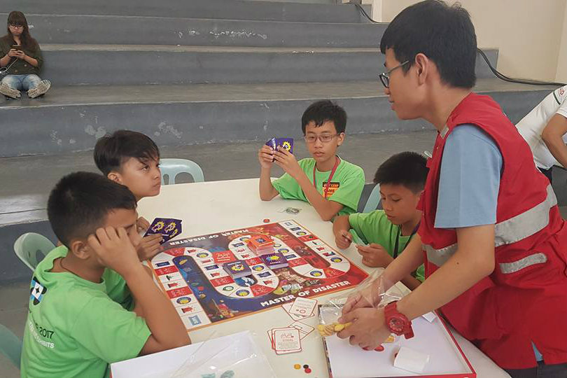 """MASTER OF DISASTER. Kids at the Batang Emergency Response Team (BERT) camp at the CAMANAVA Science and Technology Fair play the """"Master of Disaster"""" board game. Photo by ASSIST"""