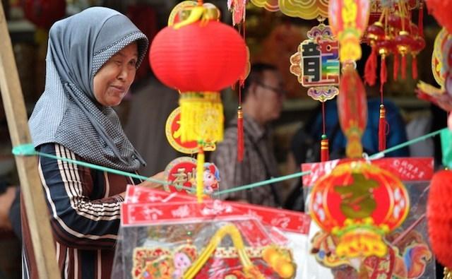 Seorang wanita di sebuah toko perhiasan Imlek. Foto oleh Bay Ismoyo/AFP
