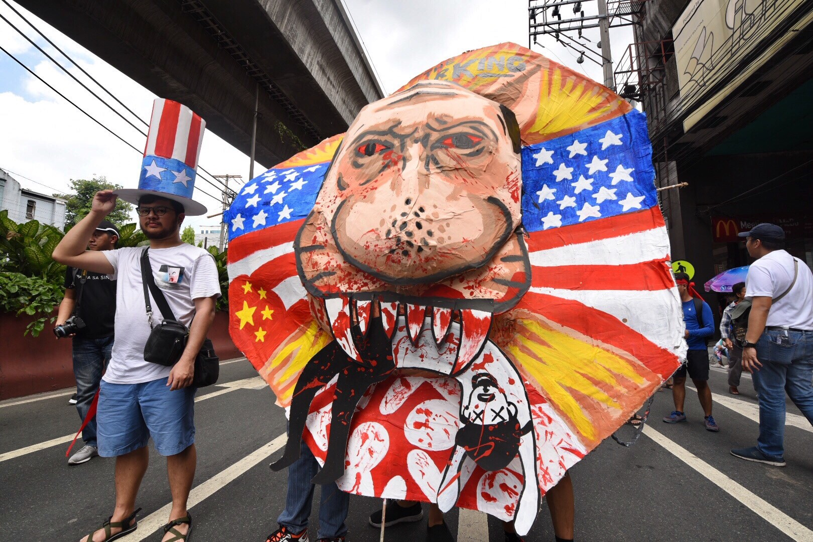 PROTEST. In this file photo during the Labor Day protest on May 1, 2018, protesters carry  an effigy depicting Duterte eating a Filipino. Photo by Alecs Ongcal/Rappler