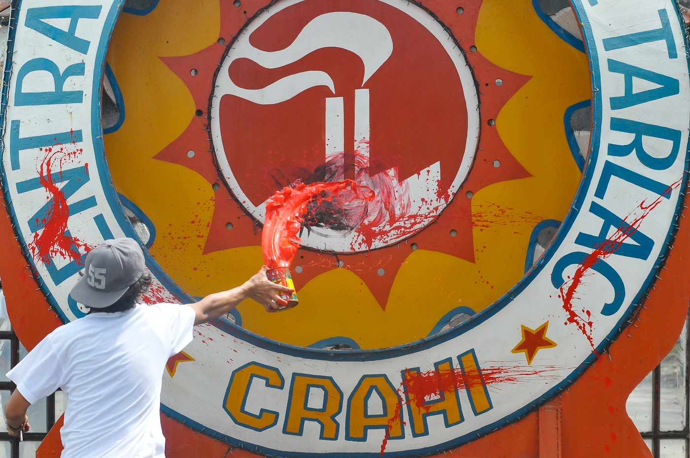 PROTEST. Activists throw red paint against the logo of the Central Azucarera De Tarlac during the 12th year anniversary of the Hacienda Luisita Massacre.