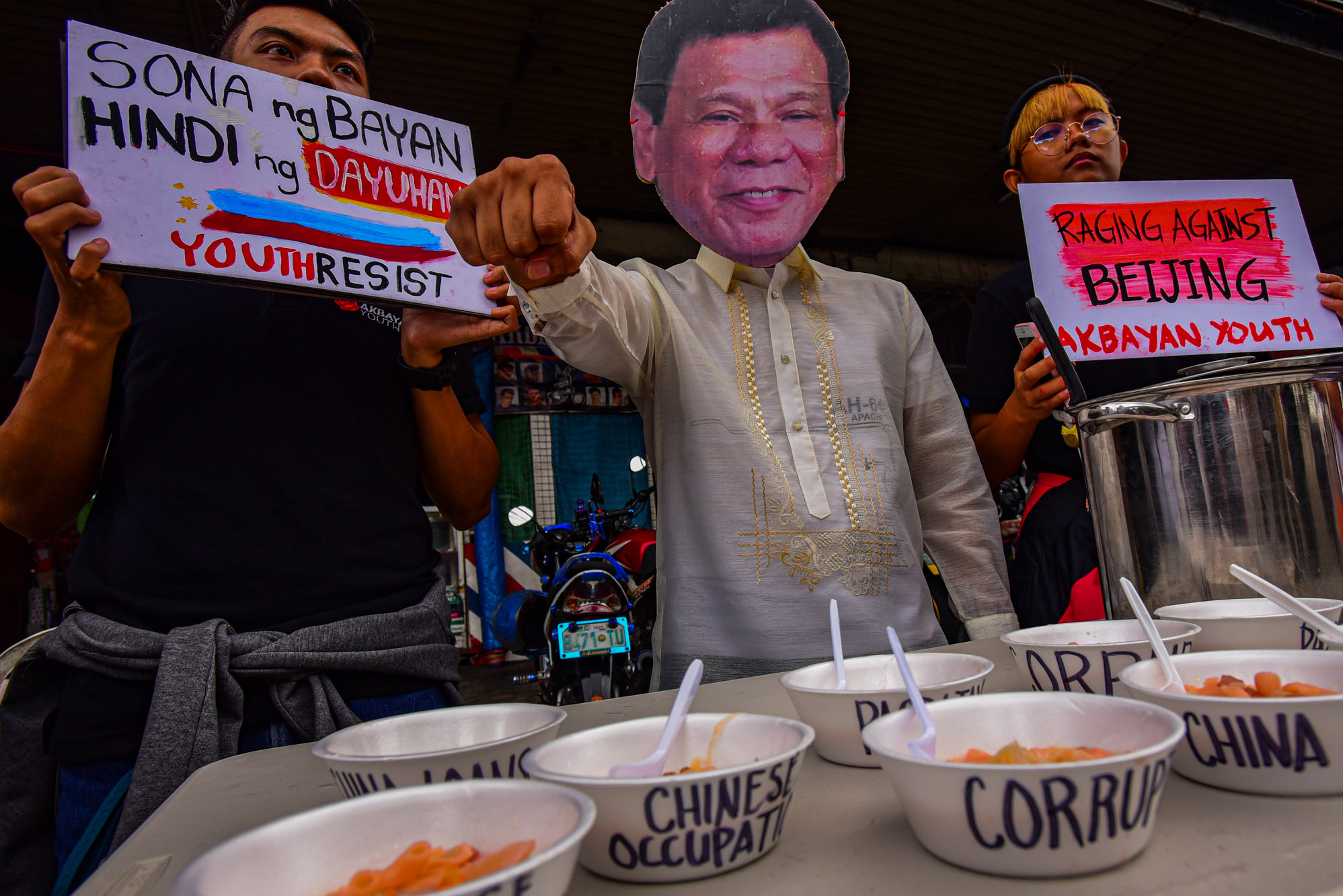 PRIORITIES. In an alternative SONA activity called SOPAS: State of the Province of China Address, a man wearing a Duterte mask gives out soup bowls labeled with Duterte's failed promises and twisted priorities. Photo by Maria Tan/Rappler