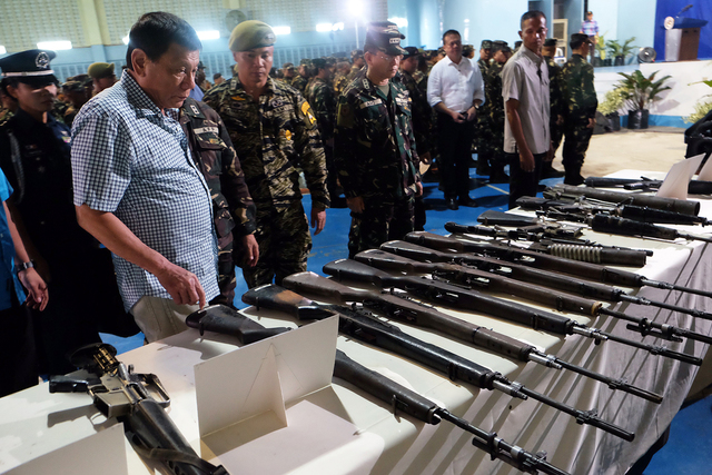 INSPECTION. President Duterte inspects the firearms recovered from the New People's Army (NPA) rebels during his visit at Camp Edilberto Evangelista in Patag, Cagayan de Oro City on August 9. Photo by Kiwi Bulaclac/PPD
