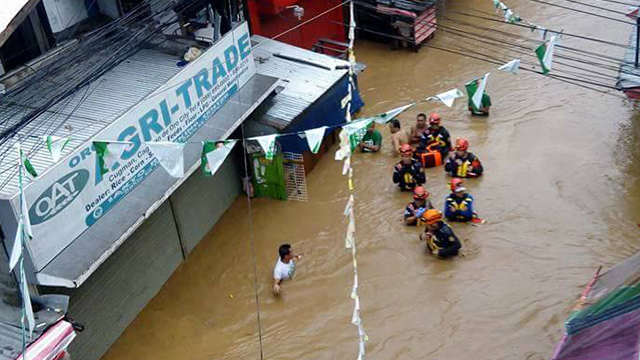 HEAVY FLOODING. Residents evacuate as flooding reach above waist-level in Cugman, Cagayan de Oro. Photo by Maricel Eduave Tawacal