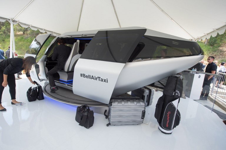 BELL AIRTAXI. An attendee gets into a full sized model of Bell's unnamed air taxi cabin concept. Photo by Robyn Beck/AFP