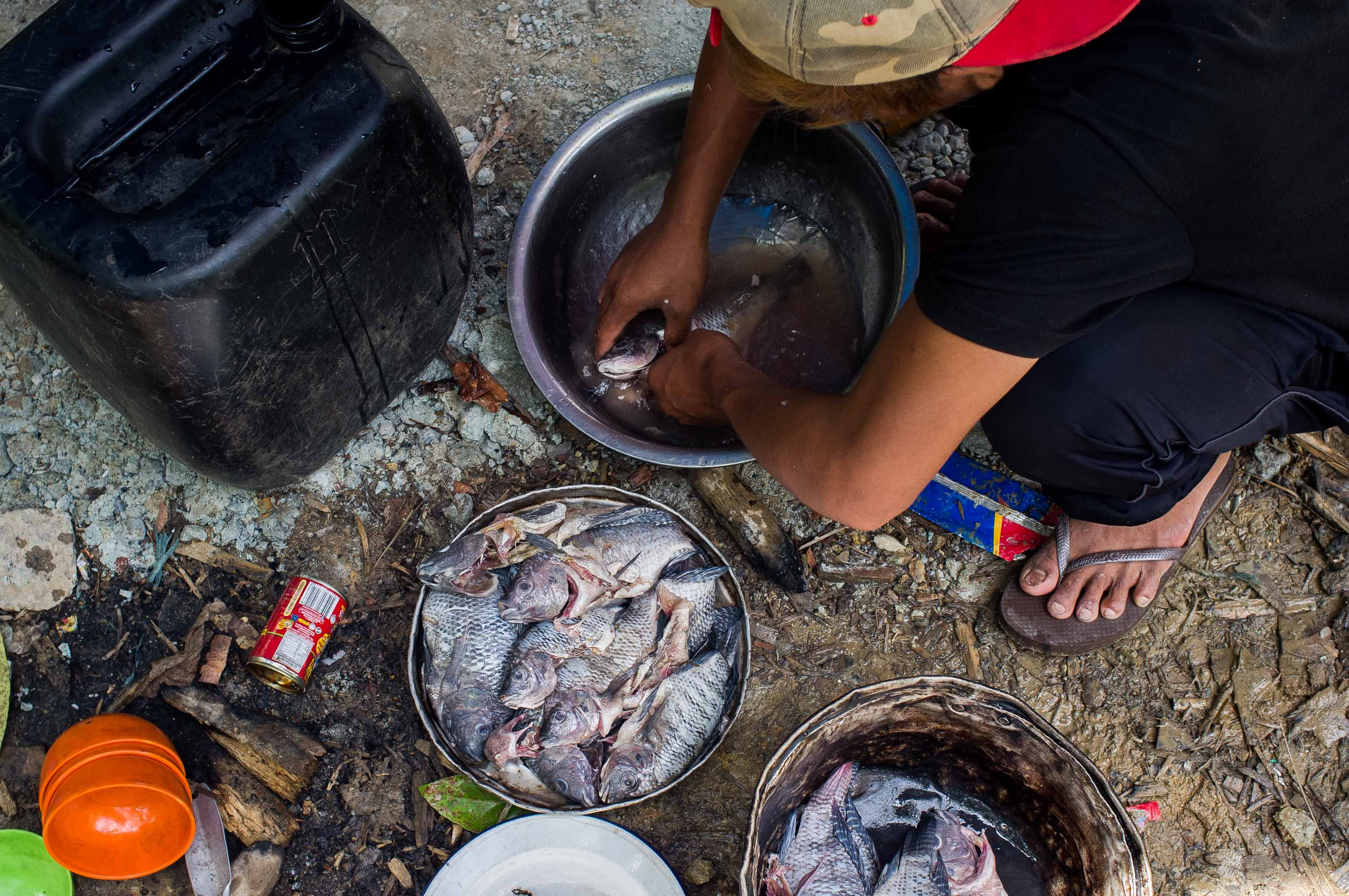 A boy prepares fish caught at the Pasig river for cooking. This photo by Mark Saludes is a finalist in the Most Outstanding Photograph category.