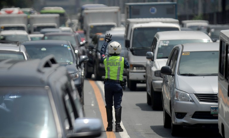 MANAGING TRAFFIC. A police officer controls traffic at Epifanio de los Santos Avenue, popularly known as EDSA in Manila on September 8, 2015. Photo by Jay Directo/AFP
