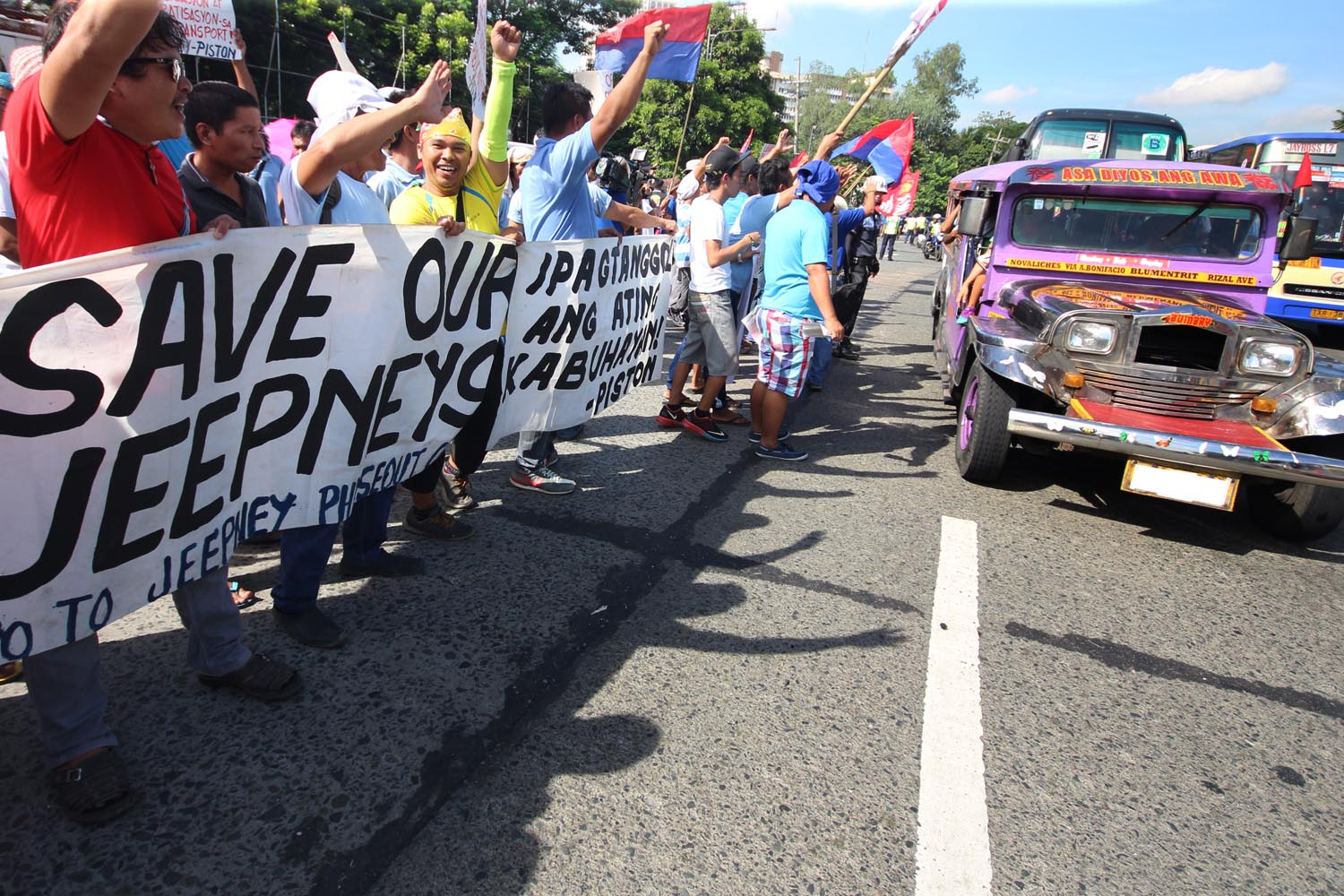 Jeepney drivers and operators belonging to transport group PISTON hold streamers against the phase-out of passengers jeepneys from 15 years old and above in a protest rally during their nationwide transport caravan at the Elliptical Road in Quezon City. Photo by: DARREN LANGIT