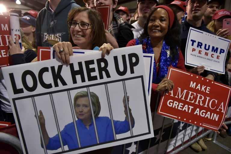 Supporters hold placards during a rally by Republican presidential nominee Donald Trump campaign after midnight, early November 7, 2016, at the Loudoun Fairgrounds in Leesburg, Virginia. Mandel Ngan/AFP