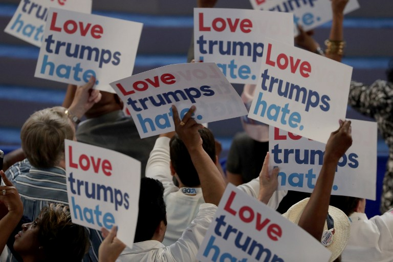 Delegates hold up signs that read 'Love trumps hate' during the opening of the first day of the Democratic National Convention at the Wells Fargo Center, July 25, 2016 in Philadelphia, Pennsylvania. Alex Wong/Getty Images/AFP