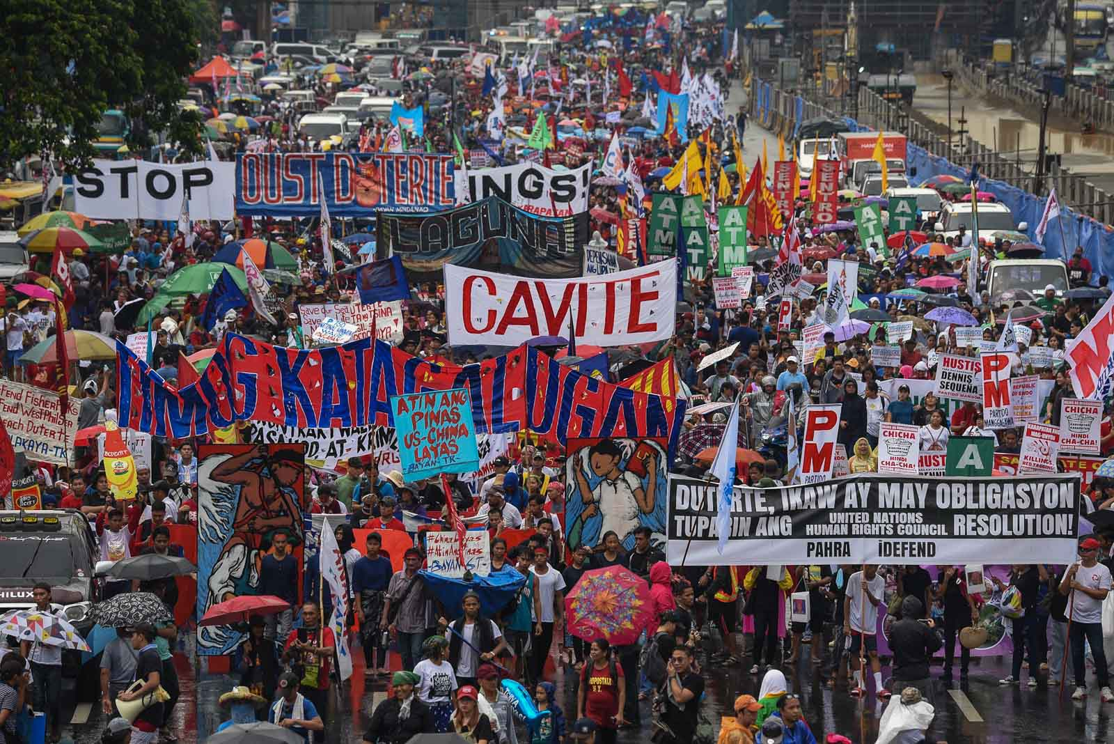 MARCH. Protesters from the United People's SONA brave the rain as they march along Commonwealth Avenue on July 22, 2019, to stage a program during President Rodrigo Duterte's State of the Nation Address. Photo by Maria Tan/Rappler