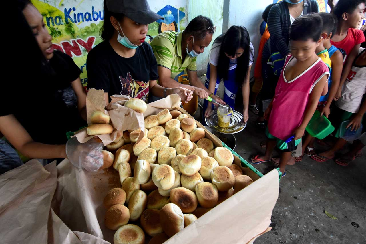 VOLUNTEERISM. Feeding program of the Parish of Our Lady of the Assumption of Guinobatan, Albay, assisted by some student-volunteers and choir members. Photo by Angie de Silva/Rappler