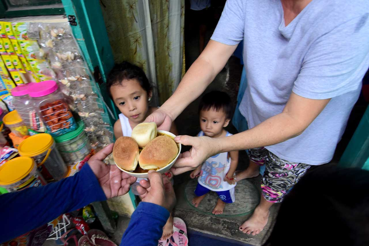 DAILY BREAD. Kids look forward to pan de sal distributed by volunteers. Photo by Angie de Silva/Rappler