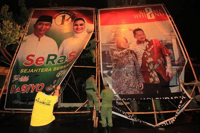 Petugas membongkar alat peraga kampanye bergambar pasangan calon wali kota/wakil wali kota dalam Pilkada Surabaya 2015 di Surabaya, Jawa Timur, pada 6 Desember 2015, yang sudah melampaui masa kampanye. Foto oleh Didik Suhartono/Antara