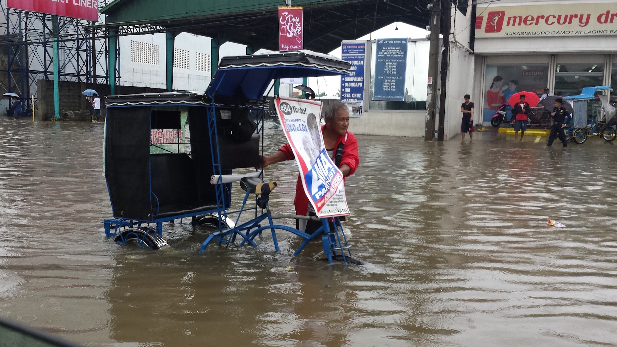 MAKING A LIVING. An elderly driver brings stranded people to their destinations along Jose Abad Santos Avenue in San Fernando, Pampanga. Photo by Jun A. Malig