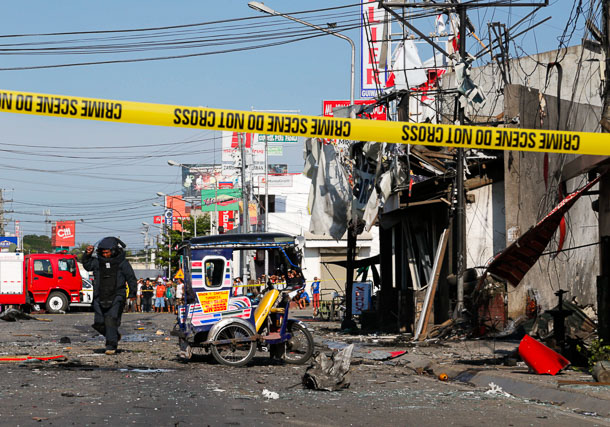 CLEARING UP. An explosives expert leaves the scene after clearing the area of secondary explosives near a bus terminal in Guiwan, Zamboanga City. Photo by Charlie Saceda/Rappler