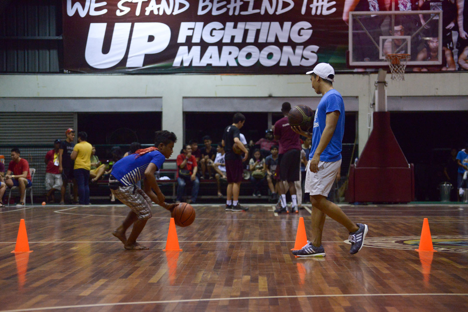 FIGHTING MAROONS. Members of UP Fighting Maroons show young Lumad basketball drills at the University of the Philippines Diliman on Monday night, October 26. All photos by Jansen Romero