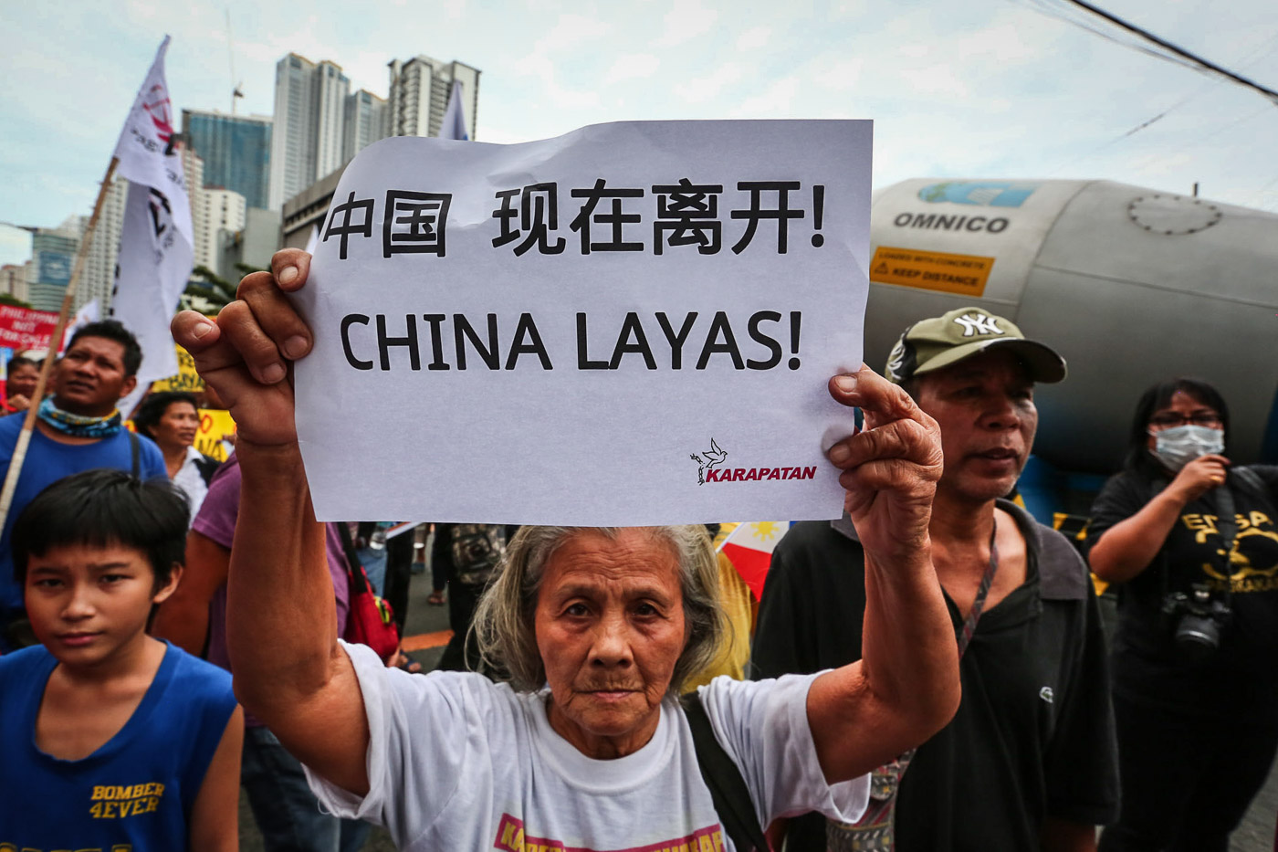 "STRONG STAND. A woman carries a sign with the words ""China layas!"" during a protest at the Chinese Consulate in light of Xi Jinping's state visit to the Philippines. Photo by Jire Carreon/Rappler"