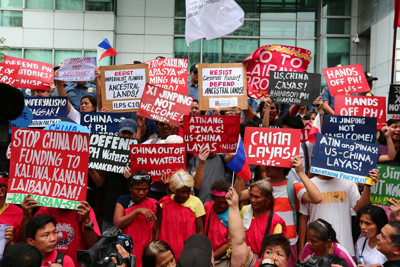 STRONG STATEMENTS. People carry signs to show their strong objection to possible deals and plans with China during the protest at the Chinese Consulate on the day of Xi Jinping's arrival in the Philippines. Photo by Jire Carreon/Rappler