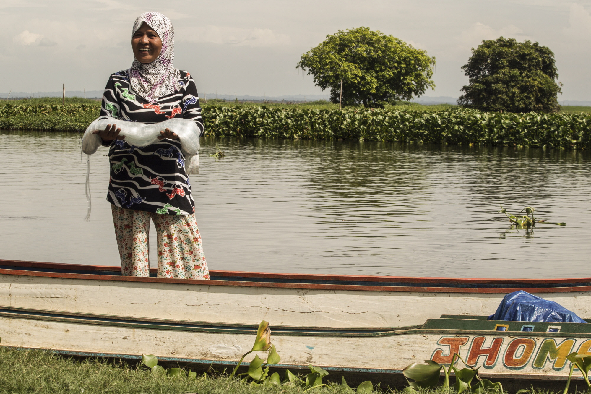NEW HOPE. A woman fisher stands by a lake in Sitio Bulogo, Baranggay Matilac in Pigkawayan municipality and shows a gill net she received through FAO. Photo by Dante Diosina/FAO