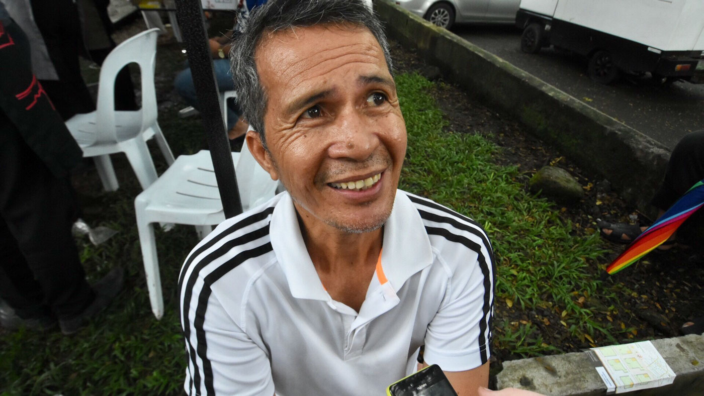SUPPORT. A proud father, Jun Laride patiently waiting for her twins outside the Palma Hall
