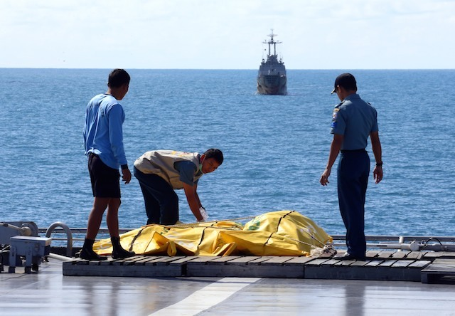 RETRIEVAL. In this file photo, Indonesian rescuers inspect body bags of victims of crashed AirAsia flight QZ8501 on board of the Navy's war ship KRI Banda Aceh at sea off Pangkalan Bun, Central Kalimantan, Indonesia, 23 January 2015. Photo from EPA