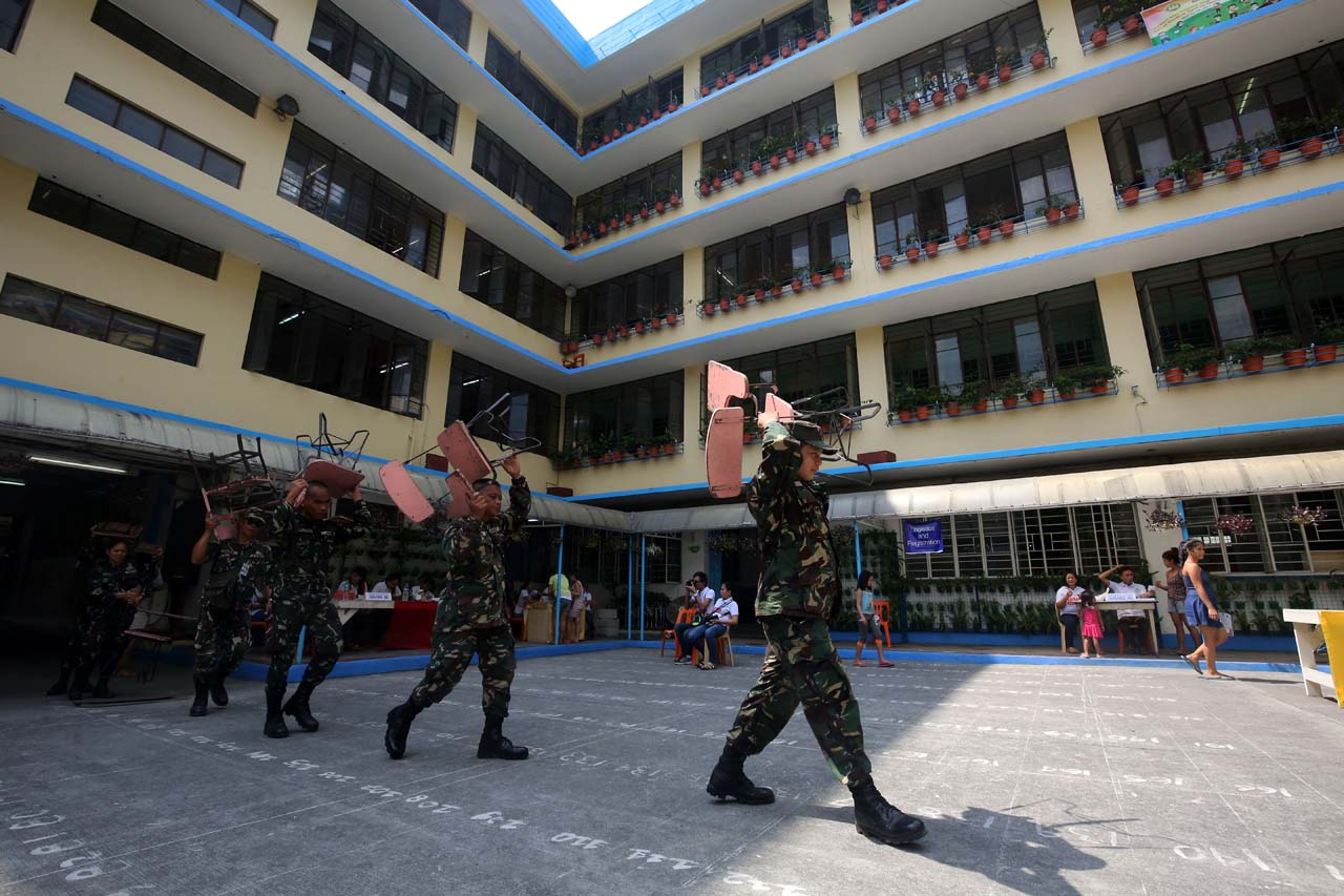 Members of the Armed Forces of the Philippines help students in carrying arm chairs during the Brigada Eskwela at the Rosario Almario Elementary School in Tondo, Manila on May 15, 2017. Photo by Ben Nabong/Rappler