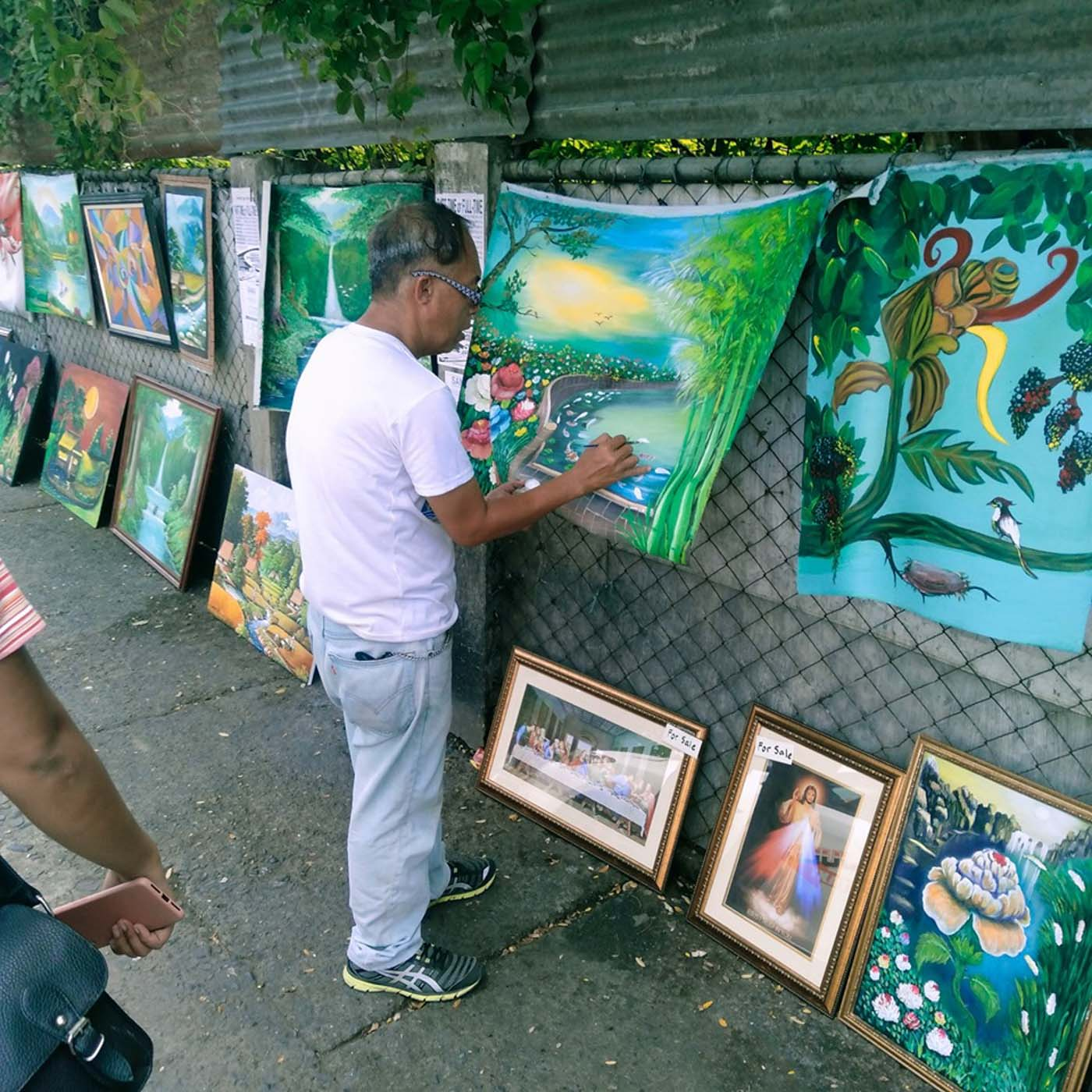 VIRAL ONLINE. Two months ago, Larry decided to regularly put up his artwork outside an abandoned building along Rizal Street, across Jaro Plaza  hanging his pieces from a rusty chain-link fence to create his own humble gallery. Photo from Sal Molinos