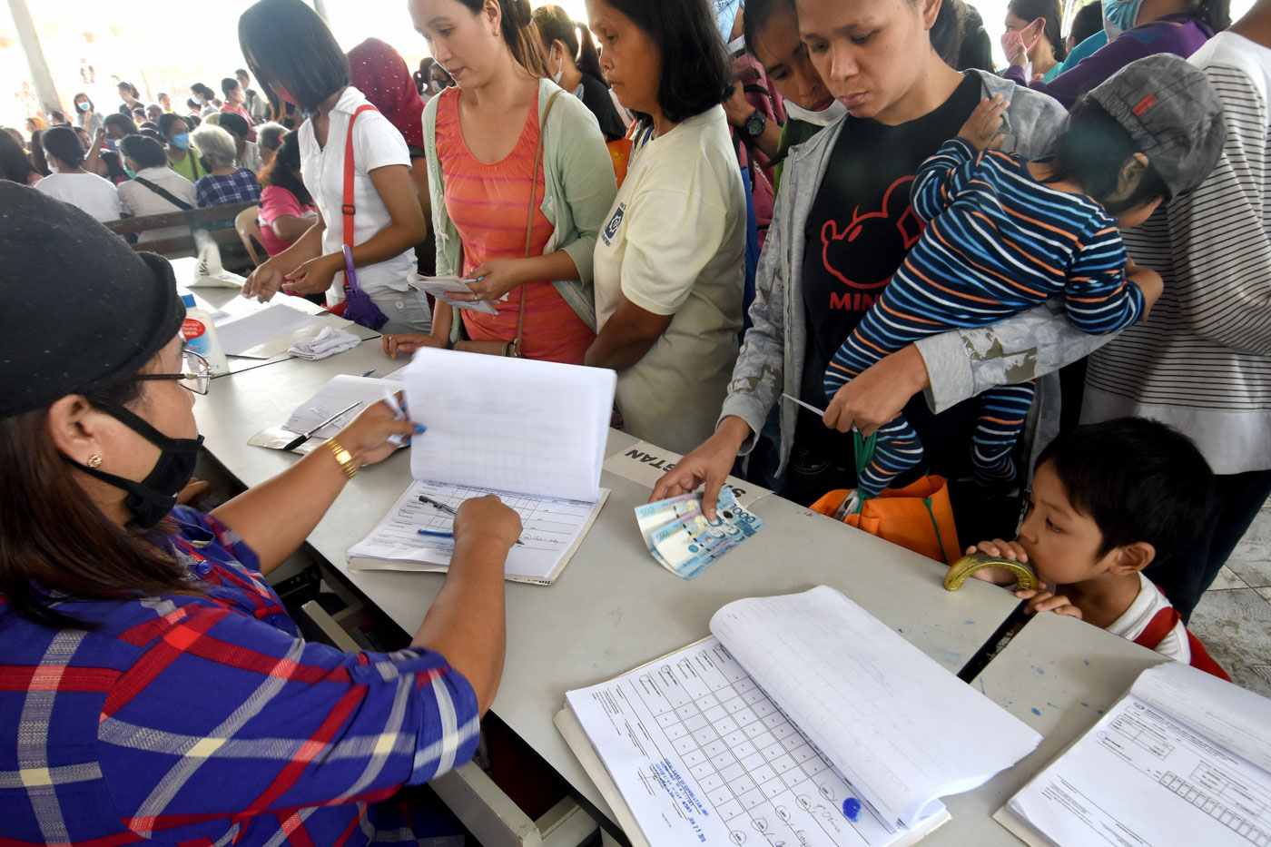 EVACUEES. Families line-up for cash transfer distribution in evacuation centers. Photo by Angie de Silva/Rappler