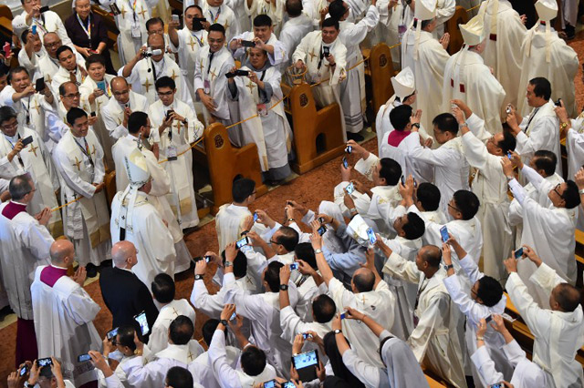 Priests take a photograph of Pope Francis as he arrives to lead a mass for local Catholic leaders at the Manila Cathedral on January 16, 2015. Photo by Giuseppe Cacace/AFP