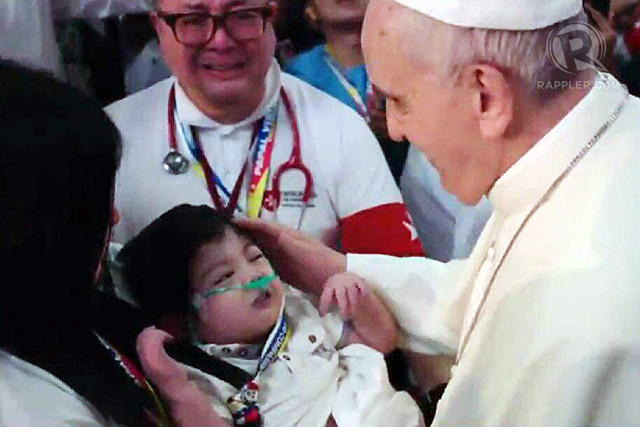 Pope Francis touches a sick child as he enters the Mall of Asia Arena for the meeting with families, January 16, 2015. Rappler photo