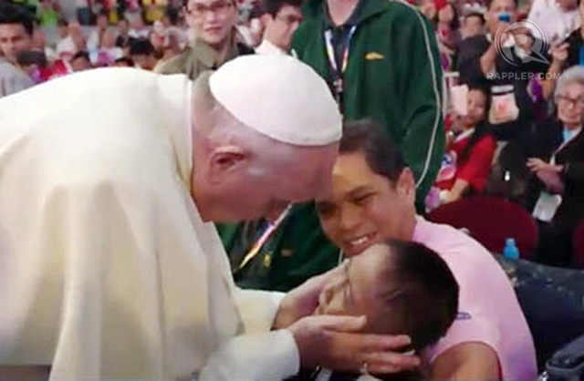 Pope Francis touches a child before the start of the meeting with families at the Mall of Asia Arena, January 16, 2015. Rappler photo