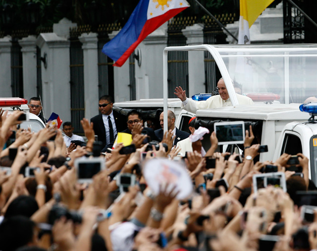 Pope Francis on a popemobile waves to well wishers at a street following his meeting at the Malacanang Palace in Manila on January 16. 2015. Photo by Dennis Sabangan/EPA