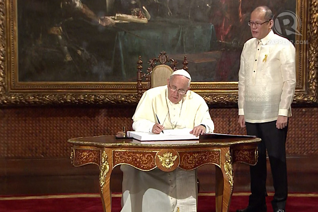 Pope Francis signs the official Guest Book at the Malacañang Palace, as Philippine President Benigno Aquino III looks on, January 16, 2015. Rappler photo