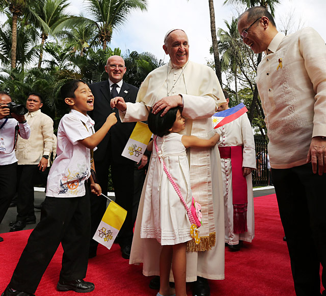 Pope Francis accompanied by President Benigno S. Aquino hugs children during a ceremony at the Malacanang Palace. Photo by Robert Vinas/ Malacanang Photo Bureau