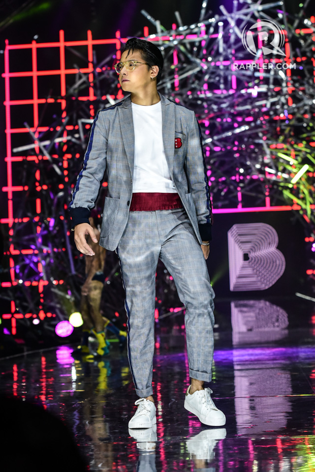 DANIEL. The actor wears a grey suit as he walks down the runway