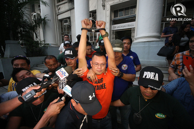 INNOCENT? Marine Lt Col Ferdinand Marcelino, a former official of PDEA, raises his handcuffs and is escorted by PDEA members as they leave the Department of Justice in Manila after attending inquest proceedings on January 22, 2016. Photo by Ben Nabong/Rappler
