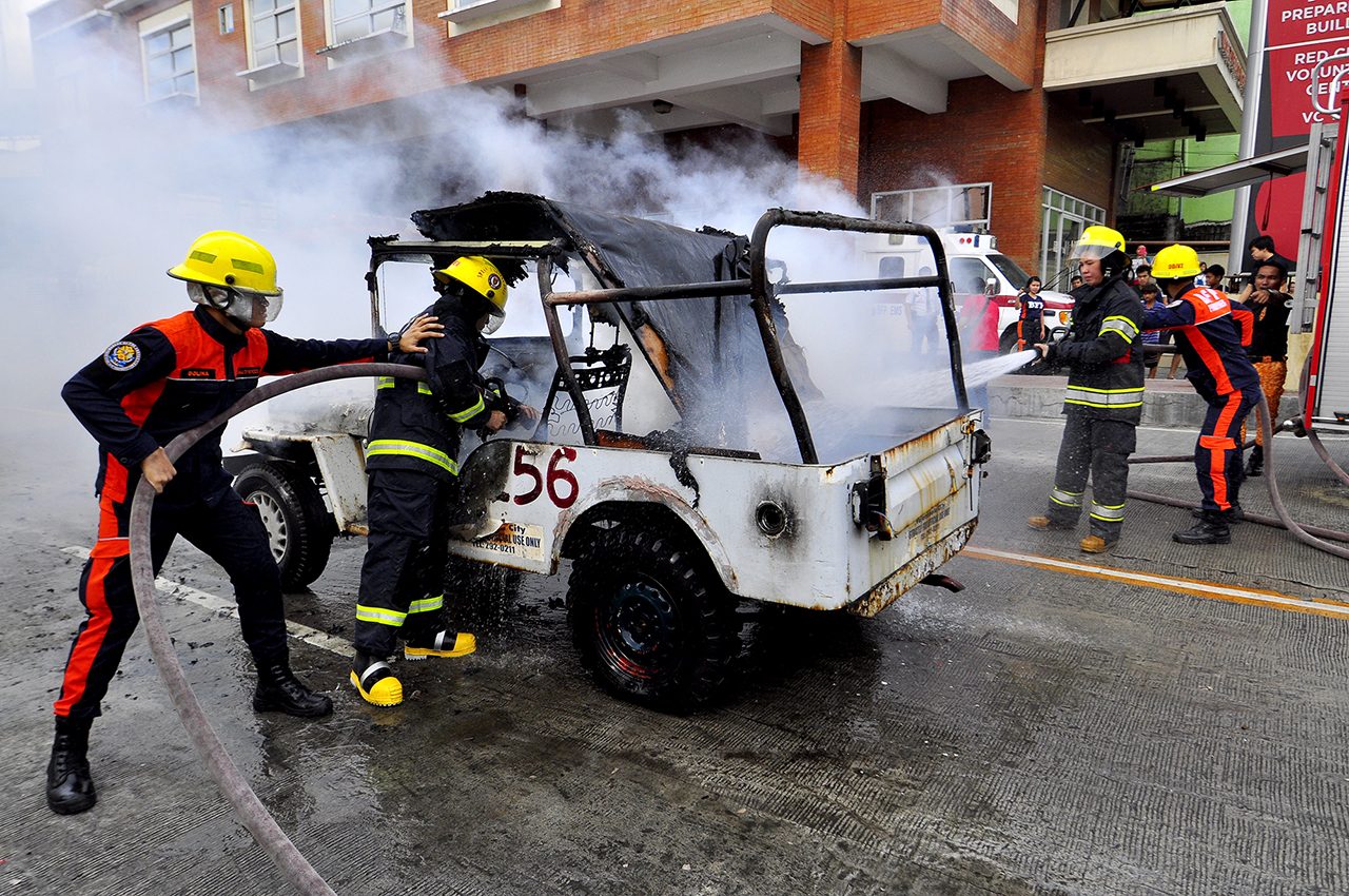 QUICK RESPONSE. Firefighters extinguish vehicle fire. Photo by Angie De Silva/Rappler