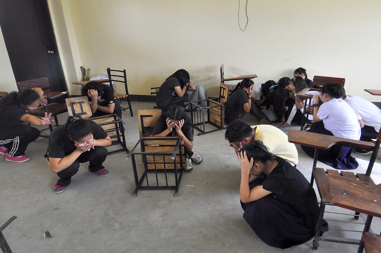 RESCUE. In this photo, students take cover as 'terrorists' attack the building. Photo by Angie De Silva/Rappler
