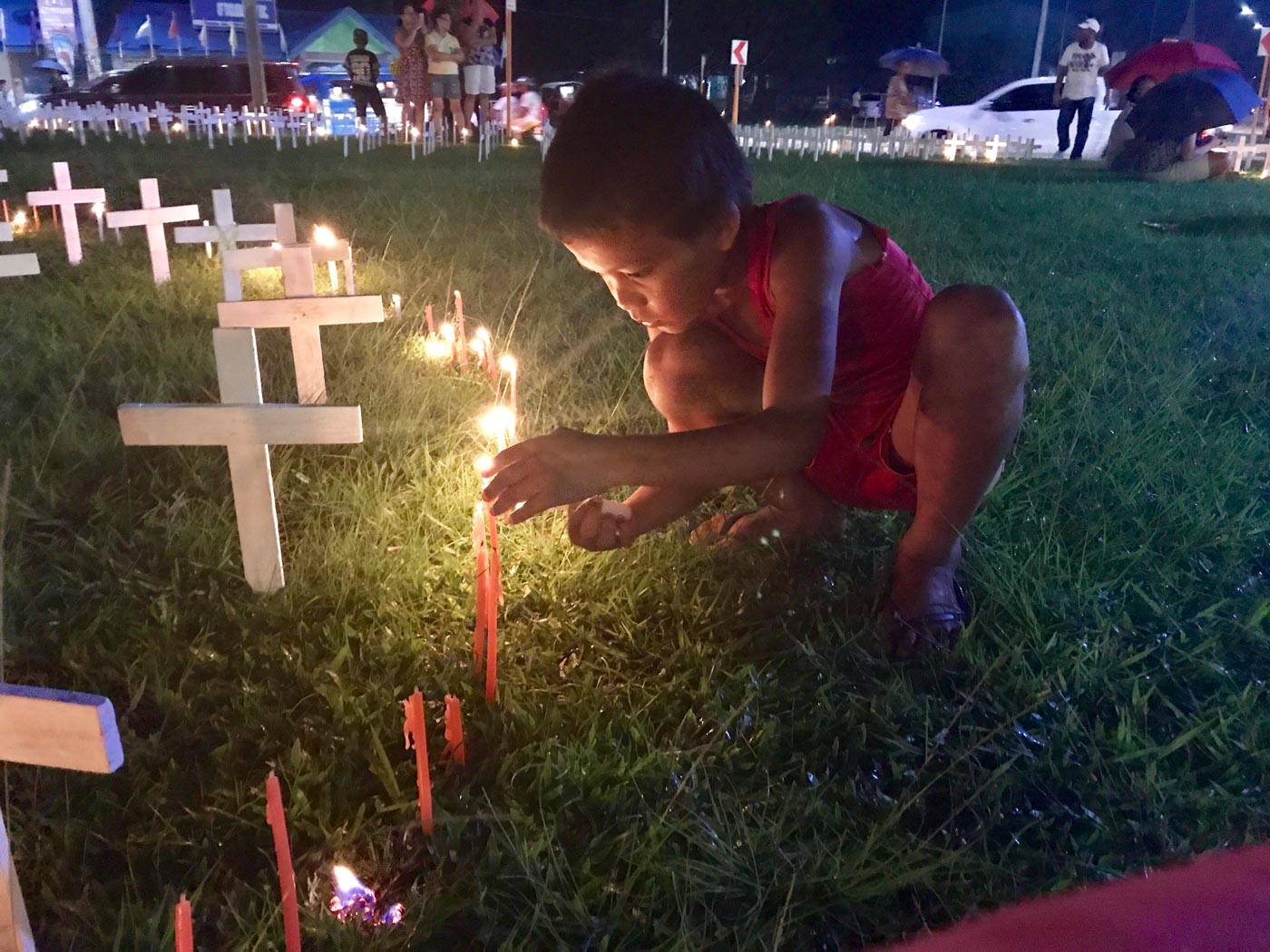 REMEMBERING. A child lights a candle to remember those who died during the disaster. Photo by Jene-Anne Pangue
