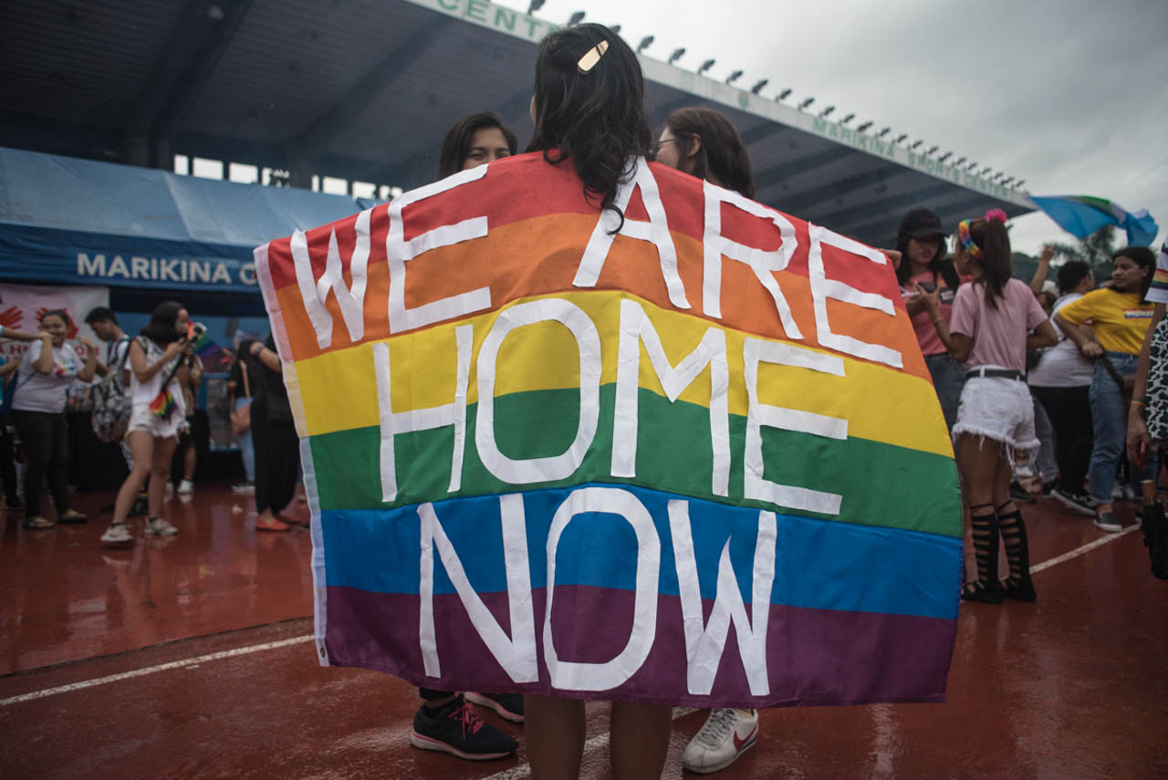 SAFE SPACE. A participant displays a Pride flag with words 'We are home now' during the Metro Manila Pride March at the Marikina Sports Center on Saturday, June 29. Photo by Rob Reyes/Rappler