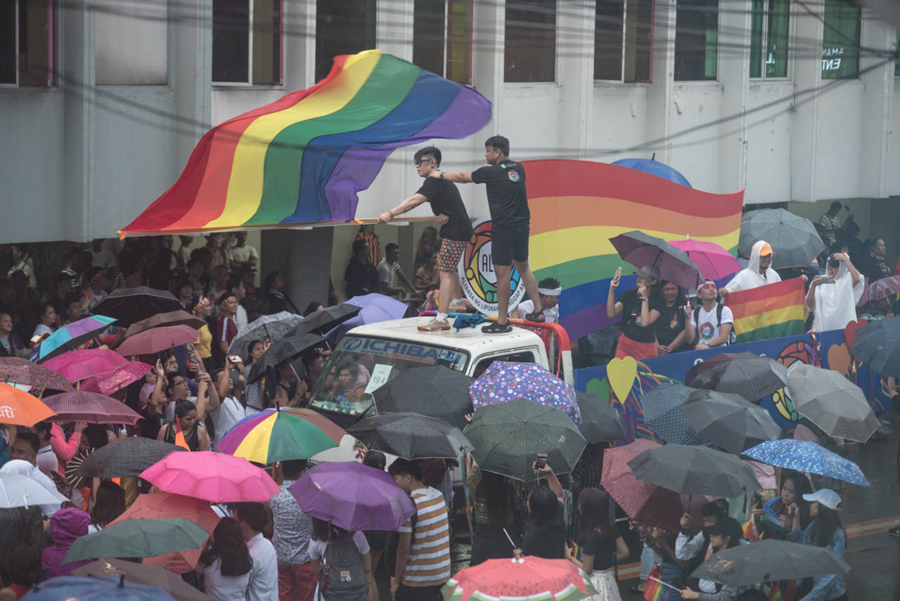 LOUD AND PROUD. A participant waves a giant Pride flag while standing at the top of one of the floats during the 2019 Metro Manila Pride March. Photo by Rob Reyes/Rappler