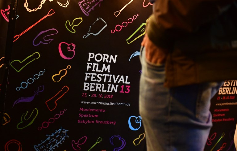 """FEMINIST PORN. A visitor stands in front of a poster announcing the Porn Film Festival in Berlin at the 'Moviemento"""" cinema on October 25, 2018. Feminist filmmakers are standing up to mass-market porn with adult movies free of male domination and gender stereotypes. Photo by Tobias Schwarz / AFP"""