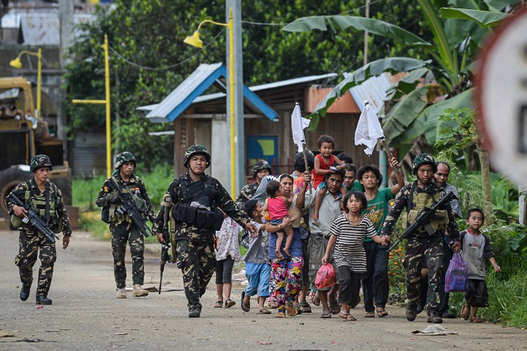 DISPLACED. Soldiers escort rescued civilians at a village on the outskirts of Marawi on May 31, 2017. Photo by Ted Aljibe/AFP