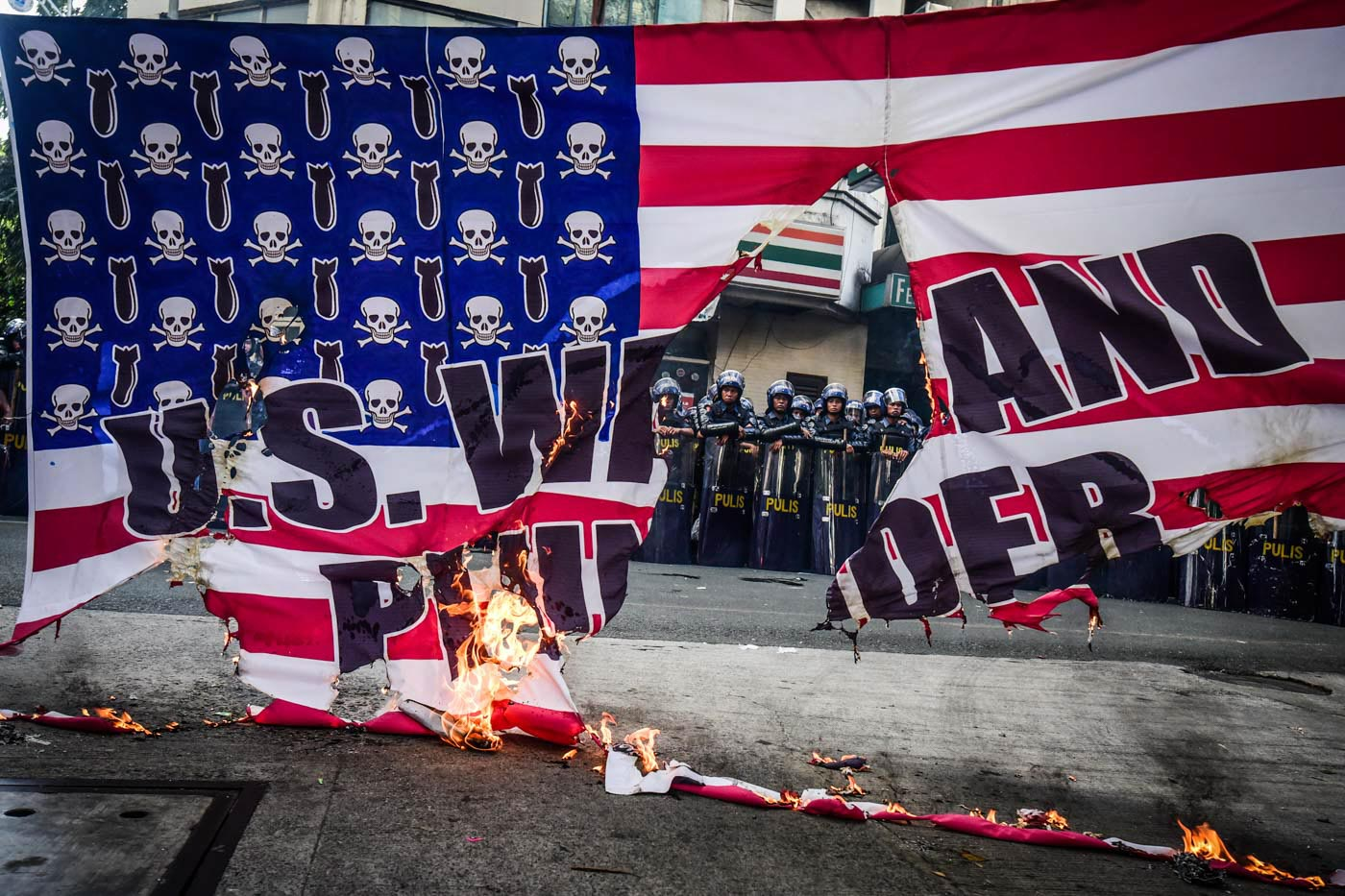 RAGE. The protesters burned down the American flag in front of the police as a sign of protest to Trump's visit to the country. Photo by Alecs Ongcal/Rappler
